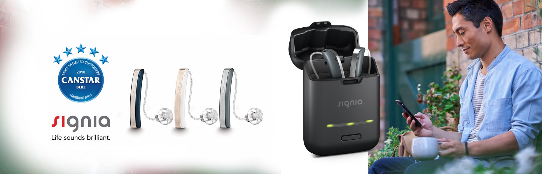 A banner image split into two parts separated by an enlarged image of the Signia styletto hearing aid on its charging case. The right image shows a man on his phone whilst the left side shows a logo of Canstar award and the three colour choices of the Styletto hearing aids.
