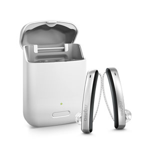 A pair of Signia Styletto Connect 3Nx hearing aid in black and silver colour sits beside the charging case on white background